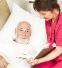 elderly man in bed with a nurse