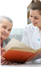 elderly woman reading book with her caretaker