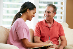 elderly man happily talking with his caregiver